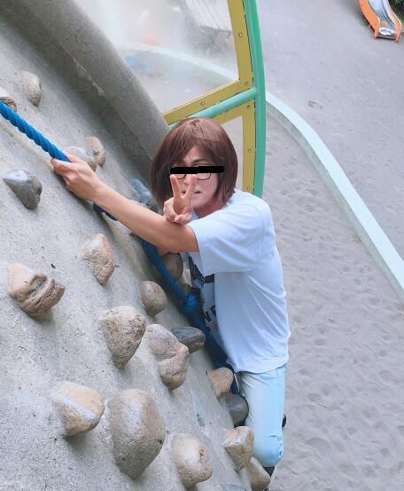 ボルダリング風の遊具を登りながらピースするみきを
